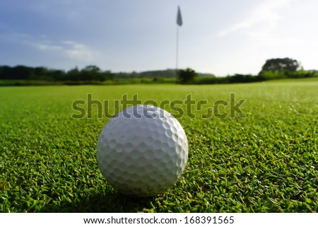 Golfball on green, ready to be putted into the hole - stock photo