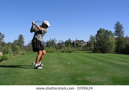 Golfer about to drive golf ball off of tee - stock photo
