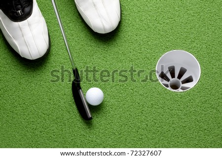 Golfer about to putt ball into cup on green - stock photo