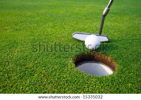 Golfer about to sink a gimme putt. Horizontally framed shot. - stock photo