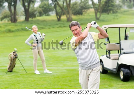 Golfer about to tee off with partner behind him on a foggy day at the golf course - stock photo