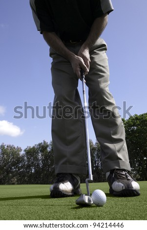 Golfer addresses a golf ball with a putter on the putting green. - stock photo