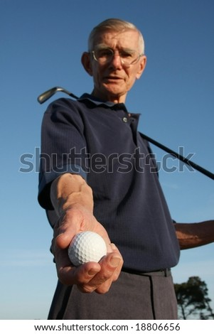 Golfer against blue sky showing his white gold ball - stock photo