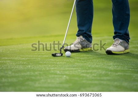 golfer aim golf ball before long putting to hole, with copy space. Morning time scene with Dew on grass.