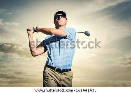 Golfer at sunset, Man swinging golf club with dramatic sunset sky  - stock photo