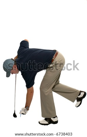 Golfer bending over to insert a tee and ball.