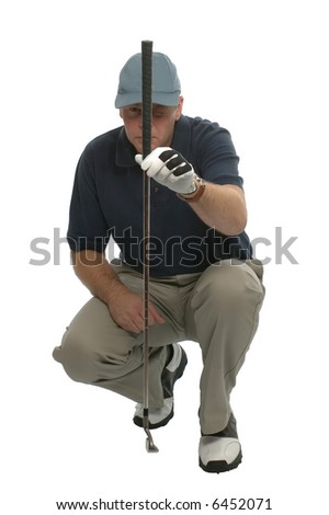 Golfer crouched down lining up a putt. - stock photo