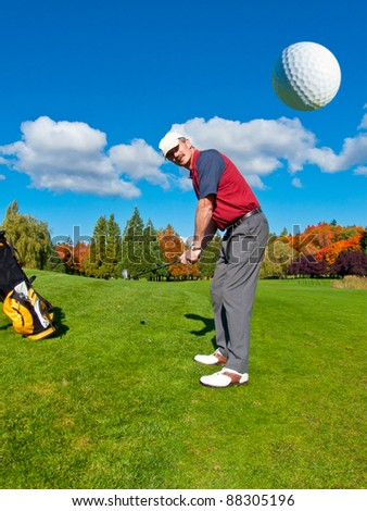 Golfer driving golf ball on beautiful golf course with deep blue sky and white clouds - stock photo