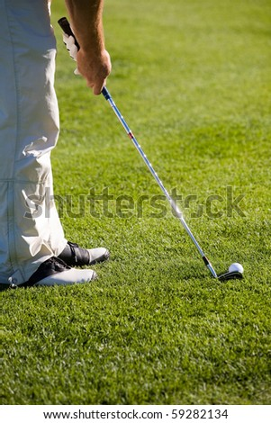 Golfer getting ready to hit the ball - stock photo