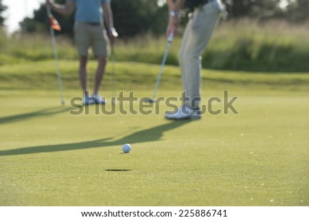 golfer goes for hole / do you think he will make it / well of course you do - stock photo
