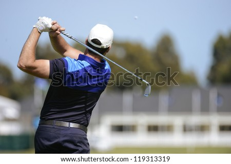 Golfer hits an fairway shot towards the club house