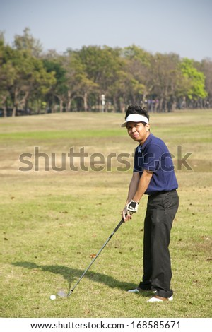 Golfer hits an fairway shot towards the club house  - stock photo