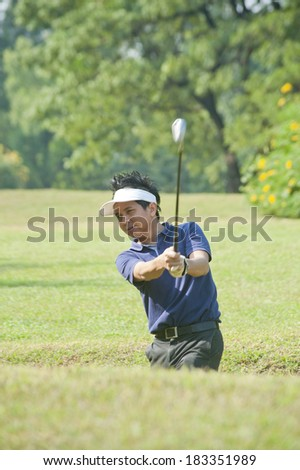 Golfer hits an fairway shot towards the club house  - stock photo