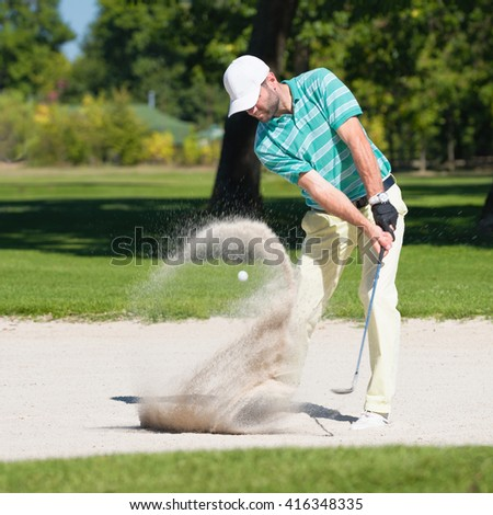 Golfer hits the ball out of sand trap. Focus on golfer, ball and sand wave in motion blur. - stock photo