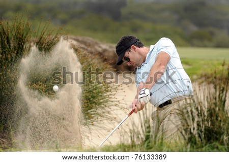 Golfer hitting a bunker shot - stock photo
