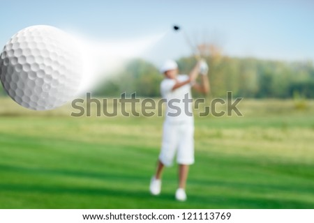 golfer hitting a flying golf ball - stock photo