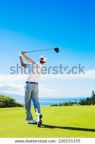 Golfer Hitting Ball with Club on Beautiful Golf Course - stock photo