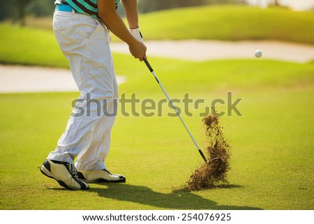 Golfer hitting ball with force. The grass distribution The blur of golf - stock photo