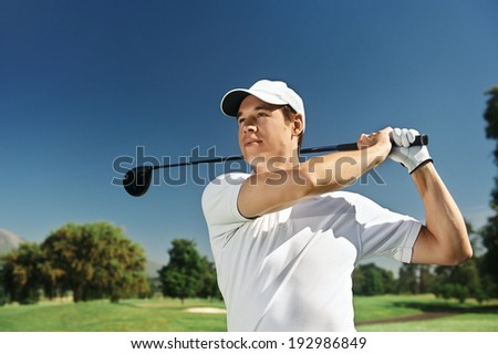 Golfer hitting driver club on course for tee shot - stock photo
