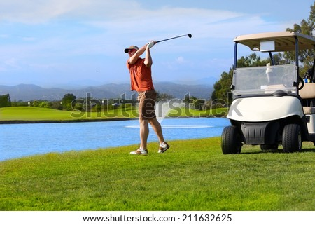 Golfer hitting golf ball next to his cart - stock photo