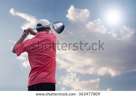 Golfer hitting golf shot on sunny  - stock photo