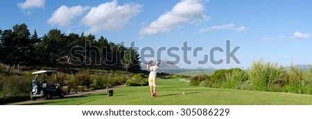 golfer hitting golf shot with club buggy cart on summer vacation - stock photo