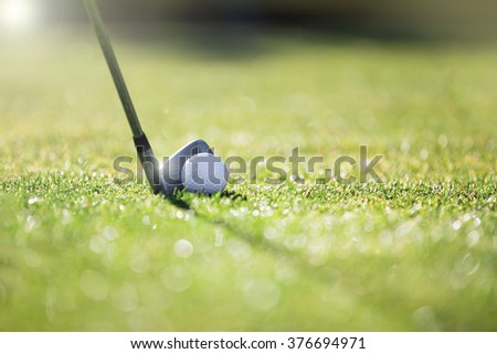 Golfer hitting iron club on course for tee shot. - stock photo
