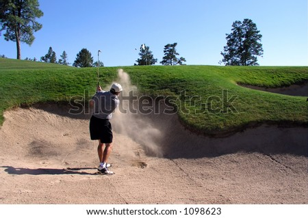 Golfer hitting out of a sand trap (3 of 3 shot action sequence) - stock photo