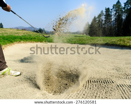 Golfer hitting out of a sand trap. The golf course is on the sand. Sand making splashes - stock photo