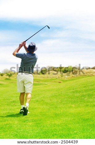 Golfer hitting the ball from the fairway. Golf club is in slight motion. - stock photo