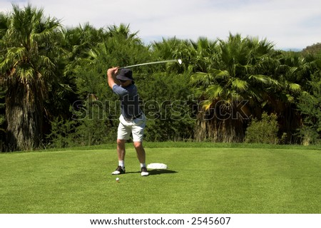 Golfer hitting the ball from the tee box. Golf club is in motion. - stock photo