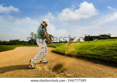 Golfer hitting the ball on the sand. Speeds Cause blurred by movement - stock photo