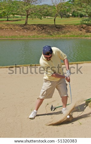 Golfer hitting the golf ball out of a sand hazard. - stock photo