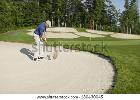 Golfer in a blue shirt blasting out of bunker onto green - stock photo