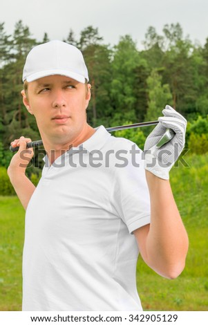 golfer in a white T-shirt and a baseball cap with golf club - stock photo