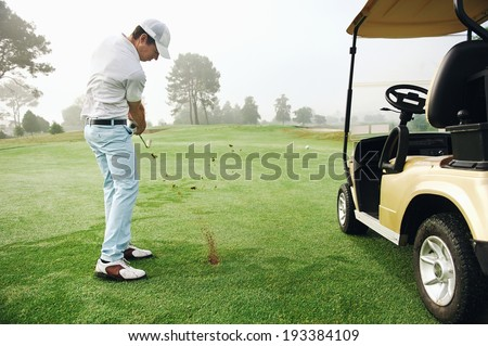 golfer in fairway with cart playing shot towards green - stock photo