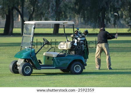 Golfer in mid swing with cart