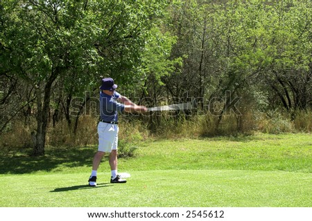 Golfer in striped shirt hitting the ball from the tee box. Golf club and arms of the golfer are in motion.
