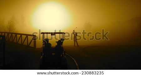 Golfer in the Golden Sunrise fog on a misty morning with a golf cart - stock photo