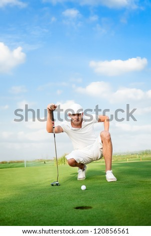 golfer lines up his eagle putt. - stock photo