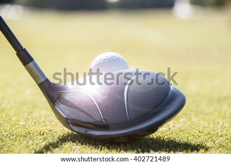 Golfer lining up a driver golf club on the tee, ready to hit the white golf ball. - stock photo