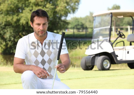 Golfer looking at the lie of his ball - stock photo