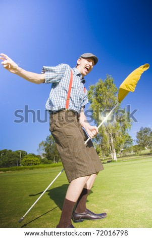 Golfer Man Grabs The Golf Hole Pole And Rides It Around The Golfing Green In Success After Celebrating A Successful Putt In Golf Victory Dance