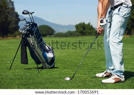 golfer man hitting golf ball from green fairway alone with bag on stand - stock photo