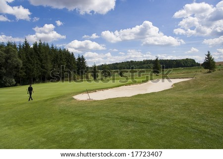golfer on a green of a beautiful golf course surrounded with bunkers with dramatic summer sky - stock photo