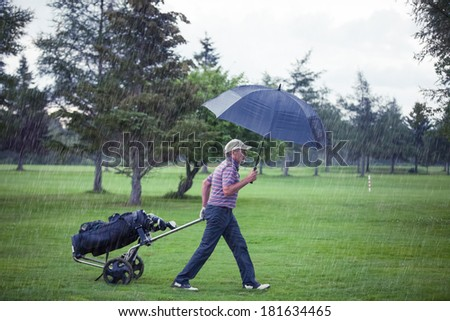 Golfer on a Rainy Day Leaving the Golf Course (the game is annulled because of the storm) - stock photo