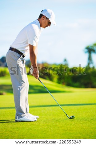 Golfer on Putting Green Hitting Ball into the Hole - stock photo