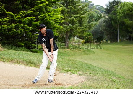 Golfer on sand trap hitting golf ball to the hole, rich adult man playing golf, strong golf shot in action,wealthy man at recreation playing golf on green course,golfer hitting ball in action - stock photo