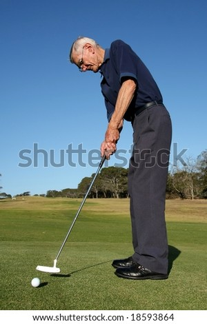 Golfer on the green playing putting stroke - stock photo