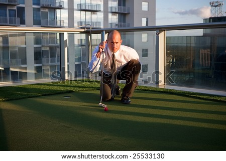 Golfer on top of a business building - stock photo